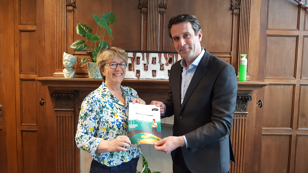 Hand over of the first publication by Gine Zwart to Oxfam Novib director Michiel Servaes